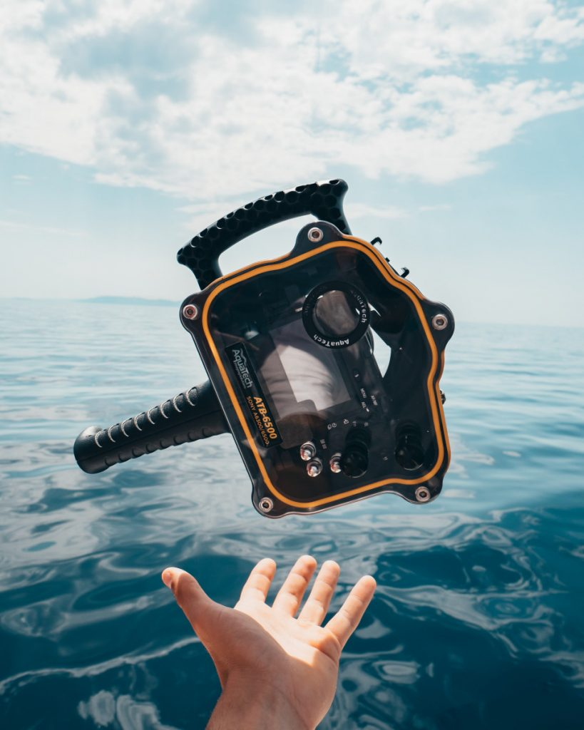 Person holding underwater camera on Komodo cruise